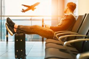 Homme dans un aéroport avec sa valise