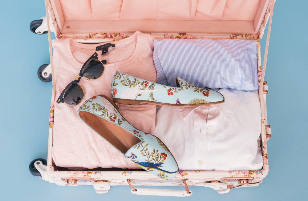 valise femme avec t-shirts roses bleux lunettes de soleil et mocassins bleus à fleurs