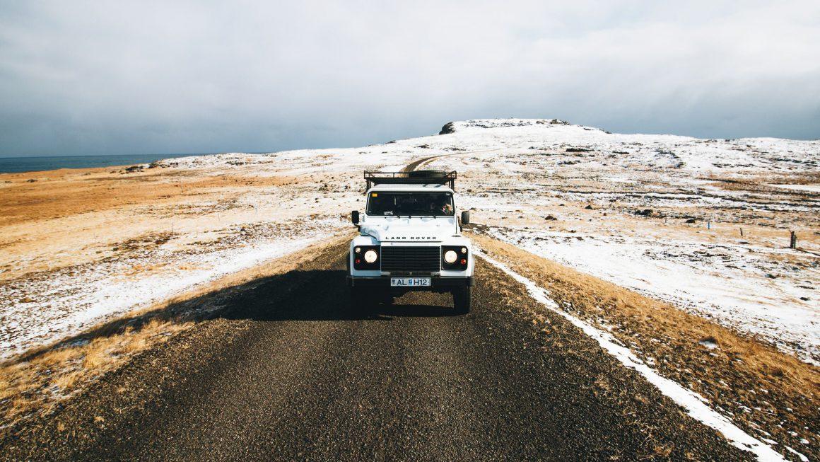Véhicule Land Rover blanc sur une route en pleine nature