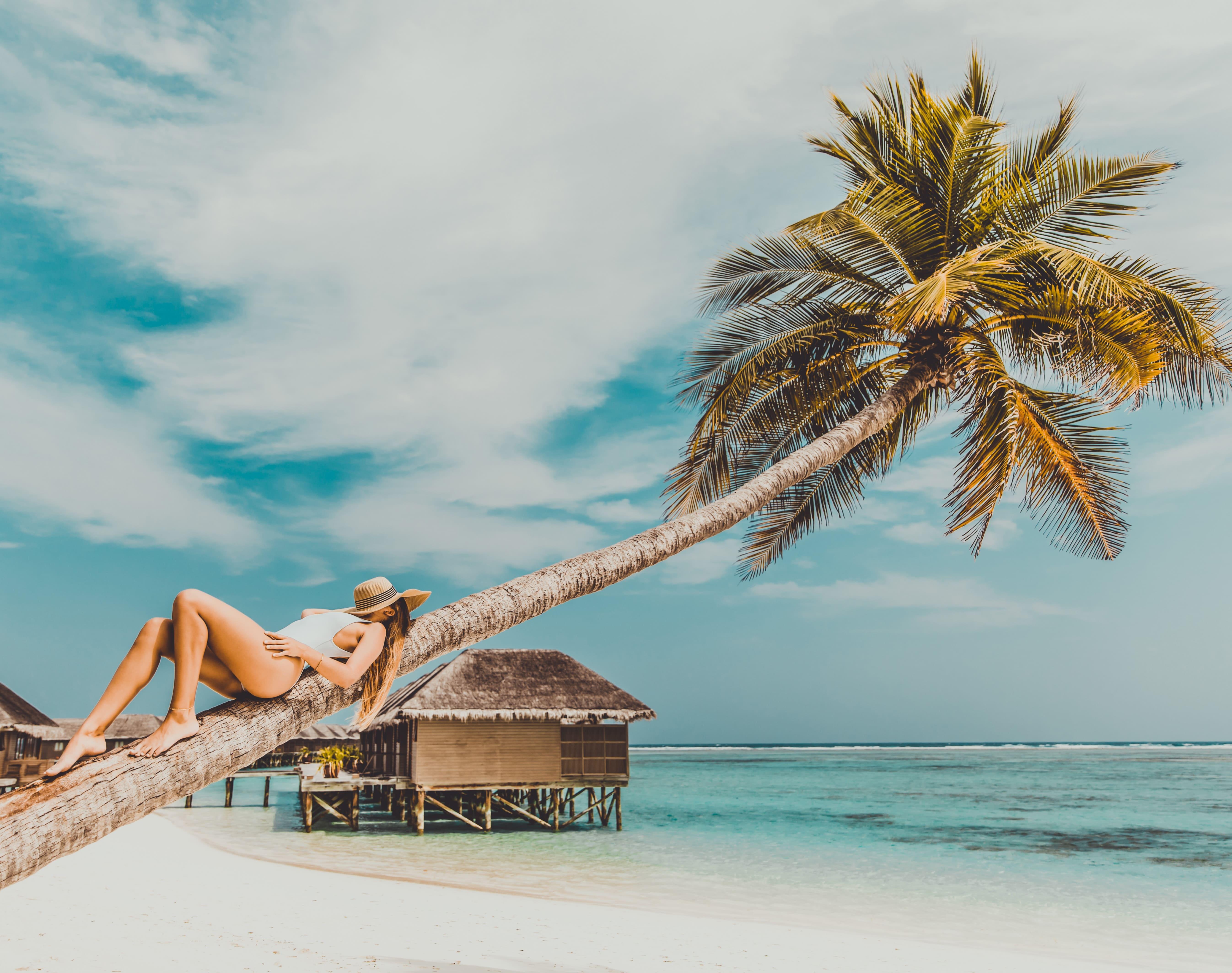 une femme fait la sieste sur un arbre aux maldives