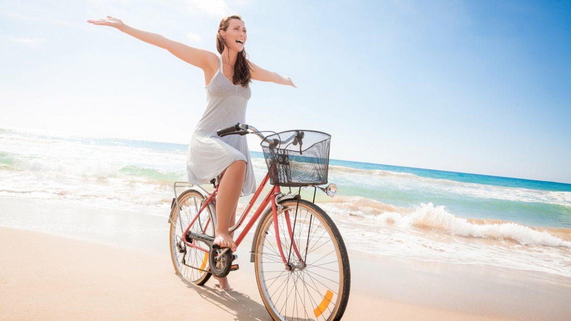 Femme à vélo sur une plage d'Oléron