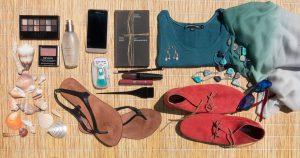 contenu d'une valise avec chaussures tongs t-shirt téléphone carnet