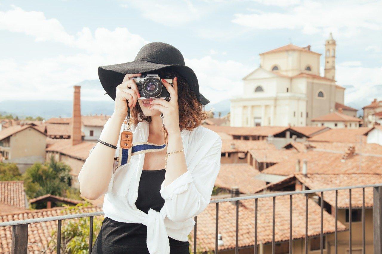 jeune femme qui prend une photo en voyage